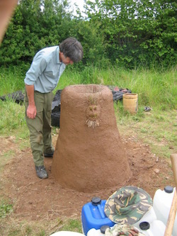 Experimental archaeology; putting the finishing touches to an iron smelting furnace.